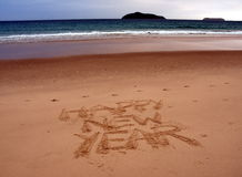 Happy New Year lettering on the beach. Happy new year written on sand at sunset. Happy New Year lettering on the beach. `Happy New Year` drawn on sand on a Royalty Free Stock Photos