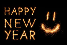 HAPPY NEW YEAR lettering and happy weird smiling smiley drawn with bengali sparkles isolated on black Royalty Free Stock Photos