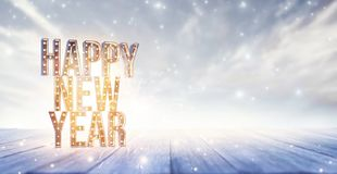 Happy New Year letters with lights on white wood background royalty free stock image
