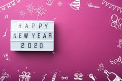 Happy new year 2020 light box with doodle party item decoration holiday festive item top view on purple background table with copy