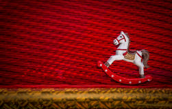 Happy New Year- Little Rocking Horse riding over textured red color background. White color, lovely rocking horse wooden toy riding over red color textured Royalty Free Stock Photos