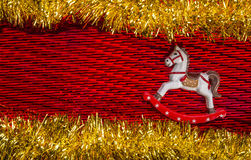 Happy New Year- Little Rocking Horse riding between yellow glossy garlands over textured red color background. White color, lovely rocking horse wooden toy over Royalty Free Stock Images