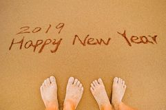 Happy new year 2019 and lover feet. Word 2019 happy new year and lover feet write on beach Stock Photography