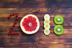 Happy new year 2018 made of fruit and berries on wooden background. Stock Photography