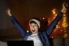 Cheerful man in santa hat celebrating new year at home with laptop royalty free stock images