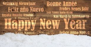 Happy new year in many languages on snowy wooden background stock image