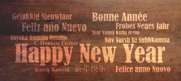 Happy new year in many languages on wooden background stock images