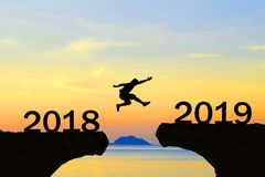 Happy New Year 2019 Men jump over silhouette. Mountains and sun royalty free stock image