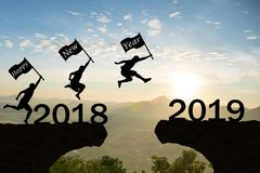 Happy New Year 2019 Men jump over silhouette mountains stock photos