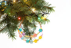 Happy New Year and merry Christmas card beaded letter garland on fir tree brunch. And garland colorful lights isolated on white background. Copyspace place for Stock Images