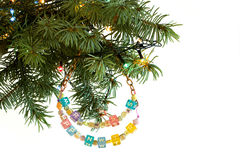 Happy New Year and merry Christmas card beaded letter garland on fir tree brunch. And garland colorful lights isolated on white background. Copyspace place for Royalty Free Stock Image