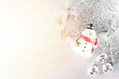 Cute santa claus doll and shiny silver ornaments on bright background Stock Photography