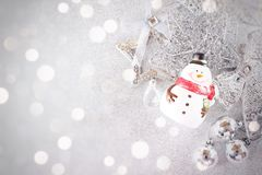 Cute santa claus doll and shiny silver ornaments on bright background Royalty Free Stock Photography