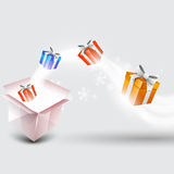 Happy New Year and Merry Christmas celebrations. Colorful gift boxes coming out from a big shiny box on snowflakes decorated grey background for Happy New Year Royalty Free Stock Image