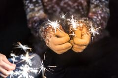 Happy new year and merry christmas concept, Hand holding a burning sparkler firework light, closeup female hand with sparkle in d. Ark stock photos
