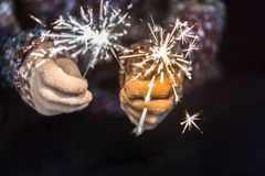 Happy new year and merry christmas concept, Hand holding a burning sparkler firework light, closeup female hand with sparkle in d. Ark stock images