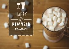 Happy new year message against a cup of hot chocolate with marshmallows. On wooden table Royalty Free Stock Photo