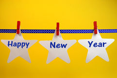Happy New Year message greeting written across white stars and red pegs on blue polka dot ribbon hanging from pegs on a line Royalty Free Stock Photos