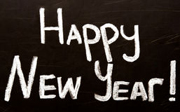 Happy New Year message greeting written on a blackboard. Happy New Year message greeting handwriting on a blackboard royalty free stock photos