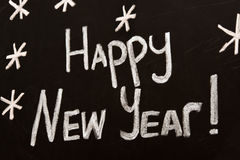 Happy New Year message greeting written on a blackboard stock images