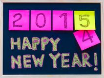 Happy New Year 2015 message hand written on blackboard, numbers stated on post-it notes, 2015 replacing 2014 Royalty Free Stock Photography