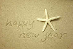 Happy new year message on the sand Stock Image