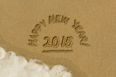 Happy New Year message in the sand. Happy new year message written in the sand on the beach Royalty Free Stock Images