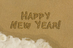 Happy New Year message in the sand. Happy new year message written in the sand on the beach Royalty Free Stock Photography