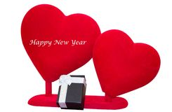 Happy new year message on soft red hearts. Happy new year message on soft velvet red hearts and black giftbox isolated on white background Royalty Free Stock Image