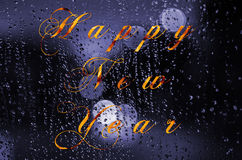 Happy new year message written on a wet glass. Night city life through windscreen: darkness and rain Stock Photography