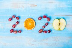 2020 Happy New Year and New You with green apple and Orange fruits on blue wood background. Goals, Healthy, Healthcare, Resolution
