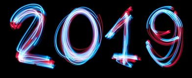 2019 happy new year number with neon lights backgrorund. Blue light image, long exposure with colored fairy lights, against a black royalty free stock photo