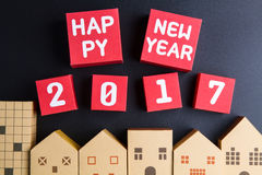 Happy new year 2017 number on red paper box cubes and home archi. Tectural model paper box cubes on black background with copy space.Christmas and New Year Stock Images