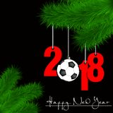 Soccer ball and 2018 on a Christmas tree branch. Happy New Year and numbers 2018 and soccer ball as a Christmas decorations hanging on a Christmas tree branch on Royalty Free Stock Photos
