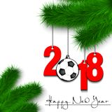 Soccer ball and 2018 on a Christmas tree branch. Happy New Year and numbers 2018 and soccer ball as a Christmas decorations hanging on a Christmas tree branch on Royalty Free Stock Image