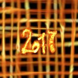 Happy new year 2017  numbers written with fire on bright burning grid bokeh background. Happy new year 2017  numbers written with fire on bright burning grid Royalty Free Stock Photography