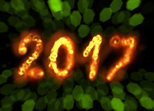 Happy new year 2017  numbers written with flame fire sparkle light on black blurred bokeh background frame Stock Photos