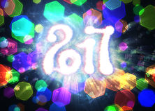 Happy new year 2017  numbers written with light on bright polygonal bokeh background full of flying digits Royalty Free Stock Image
