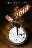 Happy New Year 2018 - Watch with Signs. Happy New Year 2018 - Old pocket watch with two wooden signs with arrows and the years 2017 and 2018 stock illustration