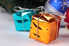 Happy New Year. Orange and blue boxes. Bright orange and blue Christmas boxes against multi coloured ornament Stock Image