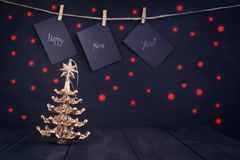 Happy new year on paper with a clothespin, hanging on a rope on a dark wooden background. Greeting card with a happy new Royalty Free Stock Photos