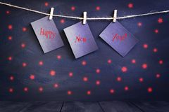 Happy new year on paper with a clothespin, hanging on a rope on a dark wooden background. Greeting card with a happy new Stock Photography
