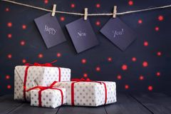 Happy new year on paper with a clothespin, hanging on a rope on a dark wooden background. Greeting card with a happy new Stock Images