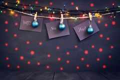 Happy new year on paper with a clothespin, hanging on a rope on a dark wooden background. Greeting card with a happy new Royalty Free Stock Photo