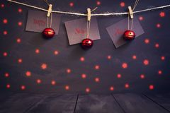 Happy new year on paper with a clothespin, hanging on a rope on a dark wooden background. Greeting card with a happy new Stock Photo
