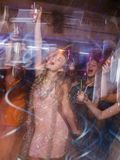 Happy New Year party in blurred motion. Joyful lady at Christmas discotheque, modern youth life, active company with drinks in night club Stock Photo