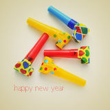 Happy new year. Picture of some party horns of different colors and the sentence happy new year on a beige background, with a retro effect Stock Images
