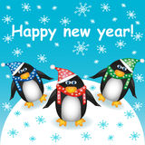 Happy new year! Postcard with three cute cartoon penguins in hats and scarves against the snow and falling snowflakes. Vector illustration Royalty Free Illustration