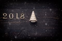 Happy New Year 2018 of real wooden figures with a fir tree on dark wooden background with snow. Stock Images