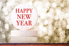 Happy new year on round wood tag with golden bokeh background,ho Royalty Free Stock Photography